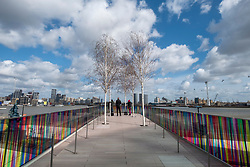 © Licensed to London News Pictures. 27/03/2021. London, UK. Visitors view the new art installation titled Hundreds and Thousands by artist Liz West for The Tide. The outdoor art work is installed on the new elevated riverside trail, The Tide, on the Greenwich Peninsula. 700m of the walkways glass balustrades are covered by a ribbon of colour. Hundreds and Thousands is presented by NOW Gallery.<br />  credit: Ray Tang/LNP