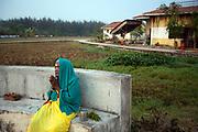 An old woman offers prayers to the sun at dawn. Tamaraikulum Elders village, Tamil Nadu, India