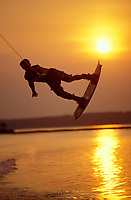 Wakeboarder jumping a wake at sunset on the lake<br /> <br /> Model Released