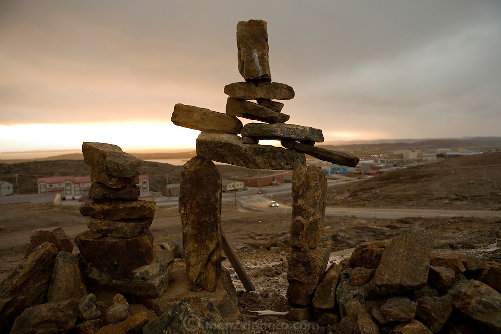 """Inukshuk (stone marker) above the town of Iqaluit, Nunavut, Canada. Iqaluit, with population of 6,000, is the largest community in Nunavut as well as the capital city. It is located in the southeast part of Baffin Island. Formerly known as Frobisher Bay, it is at the mouth of the bay of that name, overlooking Koojesse Inlet. """"Iqaluit"""" means 'place of many fish'. The image is part of a collection of images and documentation for Hungry Planet 2, a continuation of work done after publication of the book project Hungry Planet: What the World Eats, by Peter Menzel & Faith D'Aluisio.."""
