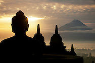 Mt. Merapi at Sunrise with Boroburdur Buddha state in foreground.<br /> The world's largest Buddhist Temple, Boroburdur, located in Central Java, Indonesia. The 9th century temple draws thousands of visitors a year who come to pilgrimage and see the amazing bas-reliefs and views. Boroburdur is surround by three volcanoes, most notably Mt Merapi which is still very active.
