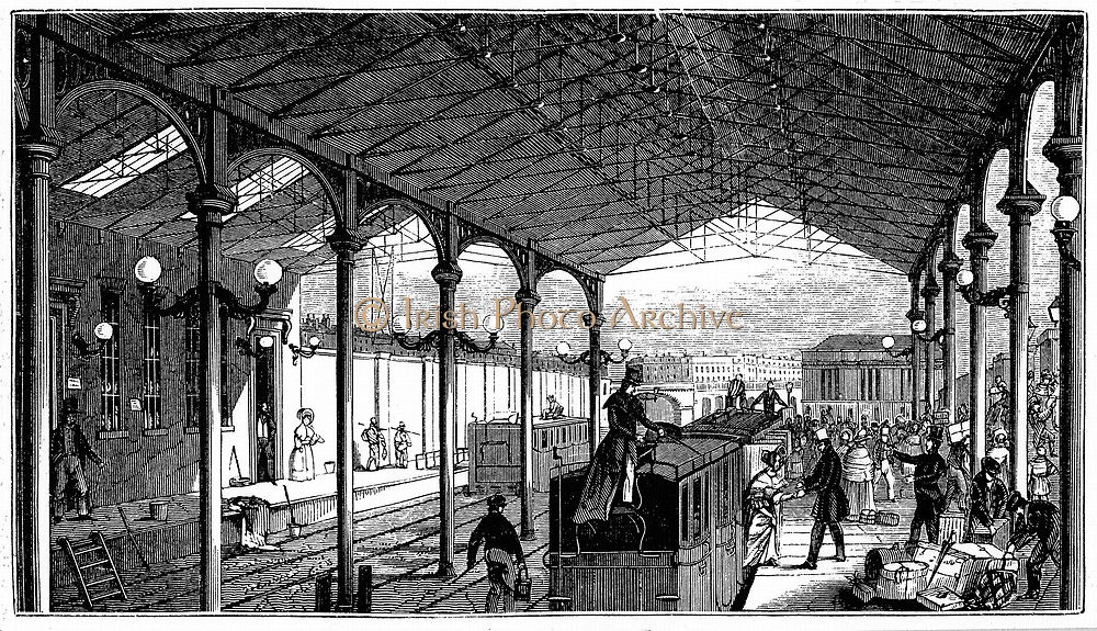 Euston Station, London terminus of the London and Birmingham Railway: man greets female passenger while luggage on roof is untied.  Engineer: Robert Stephenson. From 'London and Birmingham Railway Guide' London. 1840. Iron pillars and trusses