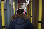 Seen from behind, a woman wearing headphones walks through a tunnel of construction foam-lined scaffolding, on 9th December 2016, in the City of London.