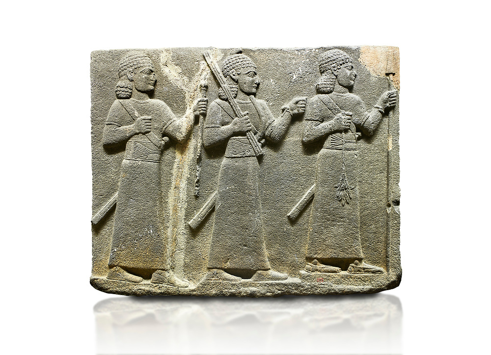Hittite relief sculpted orthostat stone panel of Royal Buttress Basalt, Karkamıs, (Kargamıs), Carchemish (Karkemish), 900-700 B.C. Warriors. Anatolian Civilisations Museum, Ankara, Turkey.<br /> <br /> Three figures each with a long dress, a thick belt and curly hair. The figure in front holds a spear with a broken tip in his left hand and a leafy branch in his right hand. The figure in the middle made his left hand a fist, and he carries a tool with his right hand at the level of his head. They are followed with a figure holding a sceptre in his left hand. All three have each a long sword at their waist. <br /> <br /> Against a white background. .<br />  <br /> If you prefer to buy from our ALAMY STOCK LIBRARY page at https://www.alamy.com/portfolio/paul-williams-funkystock/hittite-art-antiquities.html  - Type  Karkamıs in LOWER SEARCH WITHIN GALLERY box. Refine search by adding background colour, place, museum etc<br /> <br /> Visit our HITTITE PHOTO COLLECTIONS for more photos to download or buy as wall art prints https://funkystock.photoshelter.com/gallery-collection/The-Hittites-Art-Artefacts-Antiquities-Historic-Sites-Pictures-Images-of/C0000NUBSMhSc3Oo .