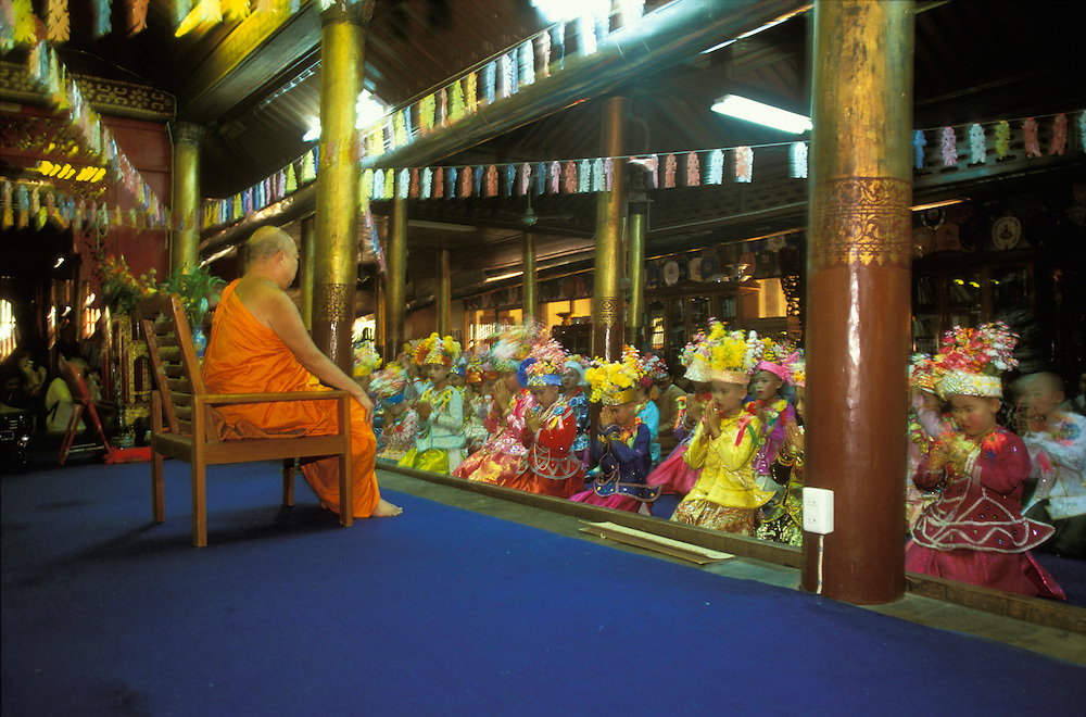 A monk receives a group of boys dressed up as princes inside a temple at Poy Sang Long, the yearly ordination of novice monks, Mae Hong Son, Thailand.