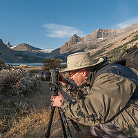 A photographer shoots beside a small inlet into  Bow Lake in Banff National Park, Alberta, Canada. Behind are the Wapta Icefield and Mount Thompson.