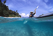 A sea kayaker explores the pristine waters of the South China Sea off the coast of a small Malaysian island.