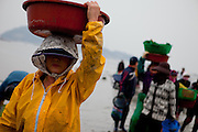 """Women carrying pots with mussels and seaweet on their heads at the open """"Mysterious Sea Road"""" in Hoedong shore (Jindo island). Jindo is the 3rd biggest island in South Korea located in the South-West end of the country and famous for the """"Mysterious Sea Route"""" or """"Moses Miracle"""". Every spring thousands flock to the shores of Jindo to walk the mysterious route that stretches roughly three kilometers from Hoedong to the distant island of Modo. Materializing from the rise and fall of the tides, the divide can reach as wide as forty meters."""