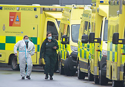 © Licensed to London News Pictures 05/01/2021.        Dartford, UK. Paramedics wearing PPE looking exhausted. A long line of ambulances outside Darent Valley Hospital in Dartford, Kent this afternoon. As the number of seriously ill Coronavirus patients continues to grow some patients are having to be transferred miles away from Kent to help with the critical care bed shortage. Photo credit:Grant Falvey/LNP