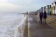 © Licensed to London News Pictures. 30/11/2013. Southwold, UK People walk near deserted beach huts on the seafront. Crashing waves on the seafront in Southwold, Suffolk today, 30 November 2013. Photo credit : Stephen Simpson/LNP