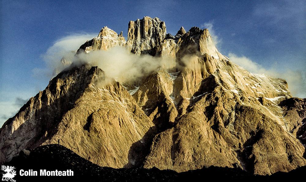 Trekker jumps for joy under Cathedral peaks, winter, en route K2, Baltoro glacier, Karakoram mountains, Pakistan.