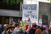 """San Francisco, USA. 19th January, 2019. The Women's March San Francisco proceeds down Market Street. A sign held high reads: """"Build a wall around Trump Tower."""" Credit: Shelly Rivoli/Alamy Live News"""
