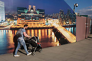 "A father pushes his child's buggy past a CCTV and a construction hoarding, a night time panorama of the Thames south bank, featuring the HQ of the intelligence service (MI6) across the river in Vauxhall. Under the gaze of a CCTV camera, the dad strides on towards a local station. The temporary hoarding will stay in place for the time that the company's new residential riverfront apartments are under construction. In the image, the building at Vauxhall Cross, is located at 85 Albert Embankment beside Vauxhall Bridge. It is known within the intelligence community as ""Legoland"" and ""Babylon-on-Thames""."