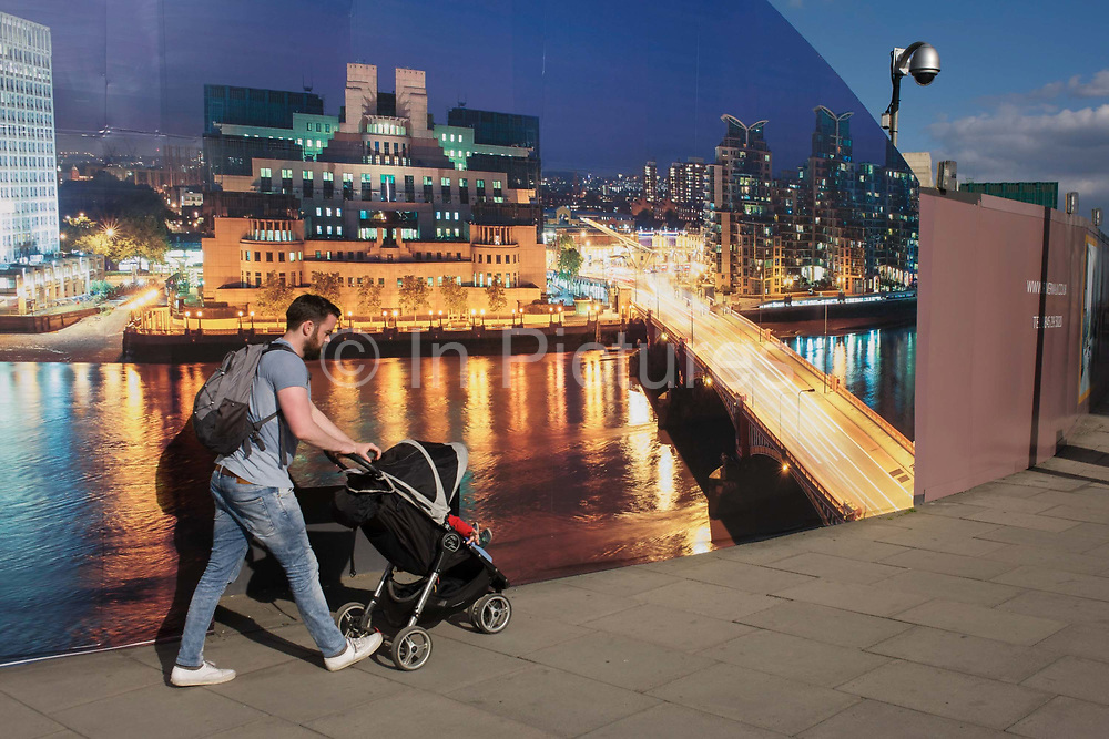 """A father pushes his child's buggy past a CCTV and a construction hoarding, a night time panorama of the Thames south bank, featuring the HQ of the intelligence service (MI6) across the river in Vauxhall. Under the gaze of a CCTV camera, the dad strides on towards a local station. The temporary hoarding will stay in place for the time that the company's new residential riverfront apartments are under construction. In the image, the building at Vauxhall Cross, is located at 85 Albert Embankment beside Vauxhall Bridge. It is known within the intelligence community as """"Legoland"""" and """"Babylon-on-Thames""""."""