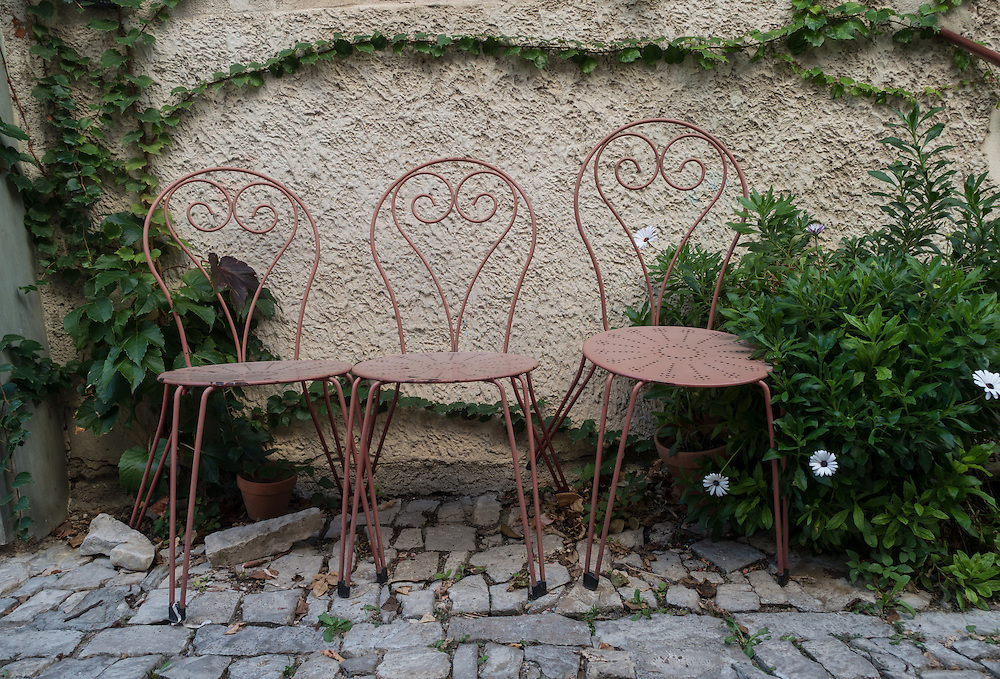 Three rust colored metal chairs with heart shaped backs sit on a grey stone paved walkway in the Provence village of Seguret, framed by a green leafy vine. Three white daisies are seen in the lower right.