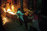 A Bulgarian copper manufacturing worker tends to molten metals in the Pirdop refinery..The Pirdop copper smelter and refinery is the biggest in the Balkans and whole of South-Eastern Europe. It was privatized in 1997 for $80,000,000 and is now owned by the German  Aurubis. It has a capacity of 160,000 tons and additional capacity of 180,000 tons worth EUR82,000,000 is being built. The factory also produces 830,000 tons of sulphuric acid and employs 1,420 workers. Pirdop is a town located in South-West Bulgaria of Sofia Province in the southeastern part of the Zlatitsa.