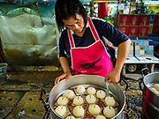 "12 FEBRUARY 2018 - BANGKOK, THAILAND: A woman cuts an ""x"" into the top of uncooked buns in a home that makes steamed Chinese buns, called ""bao"" in the Chinatown neighborhood of Bangkok. Bao are eaten at midnight on the Lunar New Year and served to guests during New Year's entertaining. Lunar New Year, also called Tet or Chinese New Year, is 16 February this year. The coming year will be the Year of the Dog. Thailand has a large Chinese community and Lunar New Year is widely celebrated in Thailand, especially in Bangkok and large cities with significant Chinese communities.    PHOTO BY JACK KURTZ"