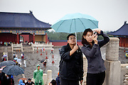 """Man holding an umbrella for his wife during she is   photographing at """"The Temple of Heaven"""" which is a complex of Taoist buildings situated in the southeastern part of central Beijing. Beijing is the capital of the People's Republic of China and one of the most populous cities in the world with a population of 19,612,368 as of 2010."""