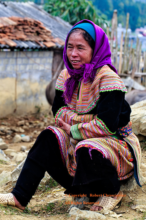 Flower Hmong Dress: A woman is huddled against the cold at the morning market, proudly displays her traditional dress of the Flower Hmong tribe, Bac Ha Vietnam.