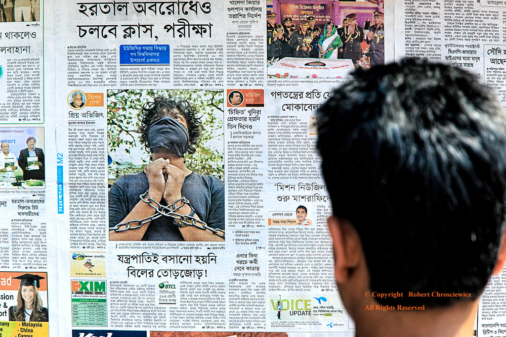 Politics of Torture:  A young man stands reading a newspaper that  depicts a man gagged and bound with chains, Dhaka Bangladesh.