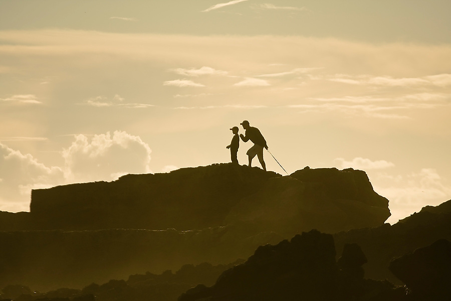 A father stands with his son on a rocky point on Laguna Beach, California.