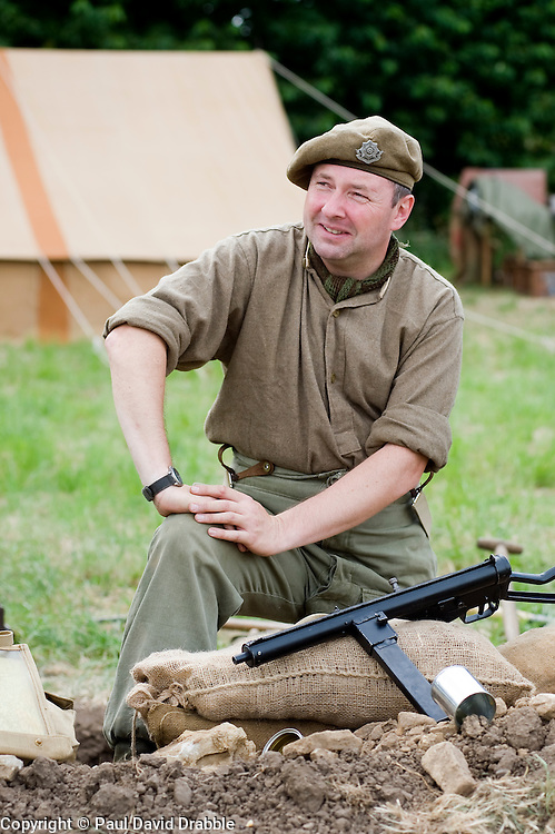 A re-enactor from the Northern World War Two Association Living History group, portraying a member of the British 5th Battalion, East Yorkshires, 50th Division, sits beside a Sten sub machine gun. SPAM 1940's Weekend Heckmonwyke near Wakefield 10 July 2010 .Images © Paul David Drabble.