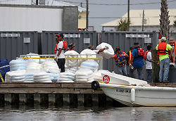 26 May 2010. Barataria Bay to Grand Isle, Jefferson/Lafourche Parish, Louisiana. <br /> Workers loading oil boom in Grand Isle. The economic impact is devastating with shrimp boats tied up, vacation rentals and charter boat fishing trips are cancelled. Oil from the Deepwater Horizon catastrophe is evading booms laid out to stop it thanks in part to the dispersants which means the oil travels at every depth of the Gulf and washes ashore wherever the current carries it. <br /> Photo credit; Charlie Varley<br /> www.varleypix.com