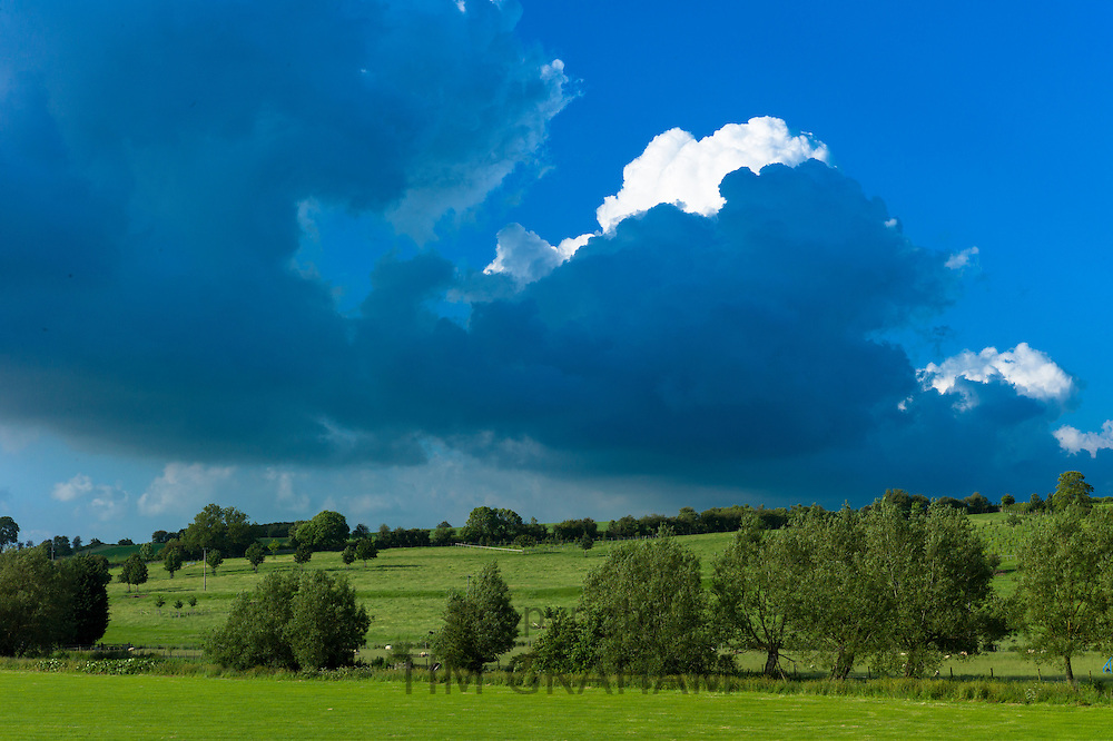 Skyscape - storm cloud darkens blue sky and loom over the landscape in summer, The Cotswolds, UK