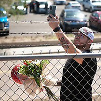 Alfredo Barron stands behind the fence at Angelo DiPaolo Memorial Stadium holding flowers and a balloon for his girlfriend Elizabeth Mejia as he watches her walk across the stage Friday morning at the University of New Mexico-Gallup Spring 2021 commencement ceremony in Gallup. The graduation ceremony was closed to the public as a COVID precaution.