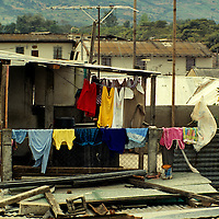 Central America, Guatemala, Antigua. Colorful clothes adorn an otherwise dull neighborhood rooftop in Antigua, Guatemala.