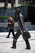 Businessman talking on the phone while passing by one of the statues honouring Perth entrepreneurs.