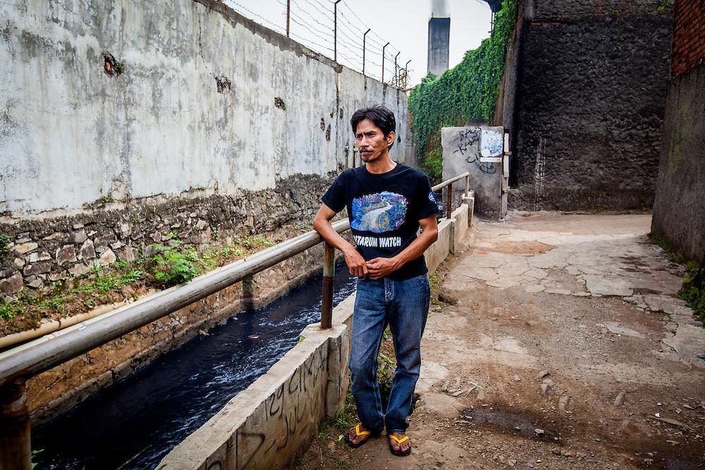 Portrait of Deni Riswandini, activist of Citarum Watch, taken behind a textile factory. Ciwalengke Village, Kabupaten Majalaya...Credit: Andri Tambunan for Greenpeace