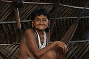 Huaorani woman, Mima sitting in a hammock which is usually the only furniture in the home.<br /> Bameno Community. Yasuni National Park.<br /> Amazon rainforest, ECUADOR.  South America<br /> This Indian tribe were basically uncontacted until 1956 when missionaries from the Summer Institute of Linguistics made contact with them. However there are still some groups from the tribe that remain uncontacted.  They are known as the Tagaeri & Taromenane. Traditionally these Indians were very hostile and killed many people who tried to enter into their territory. Their territory is in the Yasuni National Park which is now also being exploited for oil.
