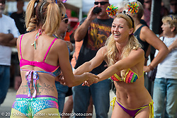 Kristi Verhoff (R) of Arizona works the Boot Hill Saloon on roller skates with a close friend on Main Street during the 2015 Biketoberfest Rally. Daytona Beach, FL, USA. October 16, 2015.  Photography ©2015 Michael Lichter.