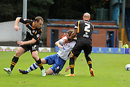 Newport County's Michael Flynn and David Pipe are left looking for the ball after a strong challenge by Bury's Andy Procter (c). Skybet Football League two match, Bury v Newport county at Gigg Lane in Bury on Saturday 5th Oct 2013. pic by David Richards, Andrew Orchard sports photography,