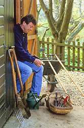 Alan Titchmarsh cleaning tools by his potting shed