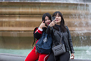 "With a background of fountains, two Asian friends take a selfie portrait with a mobile phone on which is the words ""Love You"", in Trafalgar Square, on 20th May 2019, in London, England."