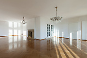 interior of an house, empty big room with fireplace, parquet floor and white walls