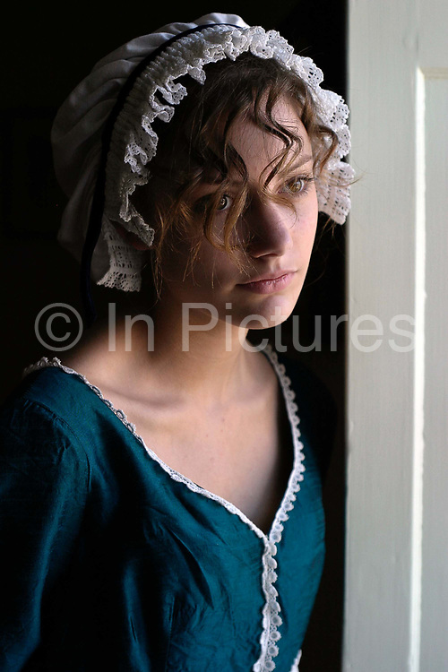 """Isabel Snowden, 18, models period costume at the Jane Austen House Museum, Chawton, near Alton, Hampshire, UK<br /> Jane Austen (16 December 1775 – 18 July 1817) was an English novelist whose realism, biting social commentary and masterful use of free indirect speech, burlesque and irony have earned her a place as one of the most widely read and best-loved writers in British literature.<br /> Around early 1809, Austen's brother Edward offered his mother and sisters a more settled life—the use of a large """"cottage"""" in Chawton village that was part of Edward's nearby estate, Chawton House. The house is now a museum devoted to Austen and her work"""
