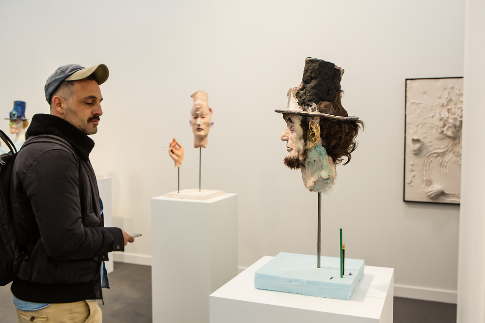 New York, NY - 5 May 2017. The opening day of the Frieze Art Fair, showcasing modern and contemporary art presented by galleries from around the world, on Randall's Island in New York City. A man appears to be stared down by a creepy mixed-media head of Abraham Lincoln by David Altmejd in the gallery of Xavier Hufkens.