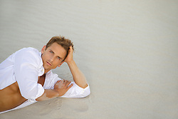 sexy man in a white shirt reclining on sand at the beach in Florida