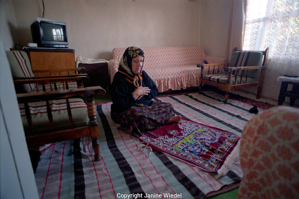 Turkish Islamic woman preying in her front room at home in town of Mulga in the Southwest of Turkey.