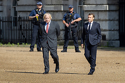 © Licensed to London News Pictures. 18/06/2020. London, UK. President Macron (R) and Prime Minister Boris Johnson walk onto Horse Guards Parade for a fly past by the Royal Air Force (RAF) Red Arrows and the Patrouille de France (PAF), the aerobatics demonstration team of the French Air Force takes place over central London. Today's events commemorate the 80th anniversary of the Second World War resistance leader General Charles de Gaulle's historic broadcast to occupied France on June 18, 1940. Photo credit: Peter Macdiarmid/LNP