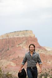 sexy cowboy walking outdoors over a mountain range