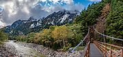 """Footbridge over Azusa River at Yokoo Sanso hut. Kamikochi (""""Upper Highlands"""") is a high valley within the Hida Mountains, in Chubu-Sangaku National Park, Nagano Prefecture, Japan. Last logged in the mid 1800s, it is now a popular nature resort. Embraced within the """"Northern Alps"""" of the Japanese Alps, the valley floor ranges from 1400 m (4600 ft) to 1600 m (5200 ft) elevation. Its highest peak is Okuhotakadake (3190 m or 10,470 ft). This image was stitched from multiple overlapping photos."""