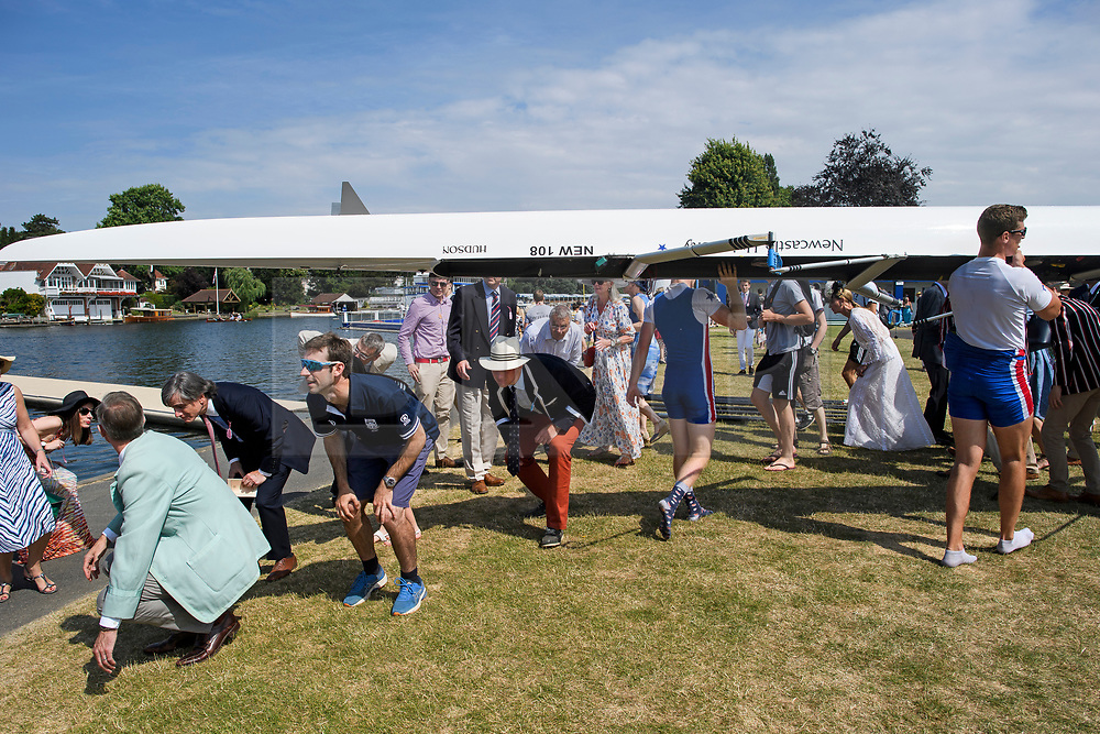 © Licensed to London News Pictures. 04/07/2018. Henley-on-Thames, UK. People duck to avoid being hit by a boat on  day one of the Henley Royal Regatta, set on the River Thames by the town of Henley-on-Thames in England. Established in 1839, the five day international rowing event, raced over a course of 2,112 meters (1 mile 550 yards), is considered an important part of the English social season. Photo credit: Ben Cawthra/LNP