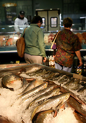01 Feb 2006. Uptown, New Orleans, Louisiana.  Post Katrina. <br /> The Whole Foods supermarket reopens amidst great celebration 5 months after  the city was hit by Hurricane Katrina. Shoppers browse the fish stall.<br /> Photo; Charlie Varley/varleypix.com