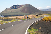 Cyclists on road leading to cone of Mount Corona volcano and Ye village, Haria, Lanzarote, Canary Islands, Spain