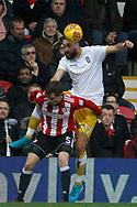 Atdhe Nuhiu of Sheffield Wednesday (R) out jumps Andreas Bjelland of Brentford (L). EFL Skybet football league championship match, Brentford v Sheffield Wednesday at Griffin Park in London on Saturday 30th December 2017.<br /> pic by Steffan Bowen, Andrew Orchard sports photography.