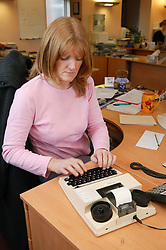 Single parent at work sitting at a desk and using a minicom in her office,